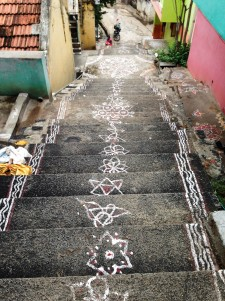 Stairs down to the street, covered in painted kolams.