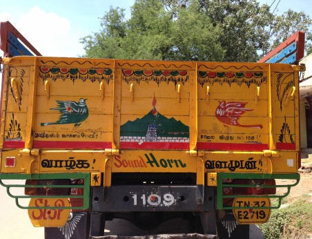Picture of the back of a truck with decorative painting. The central image is of Arunachala with the sacred fire on the top, and the temple in front. Sound Horn is below.