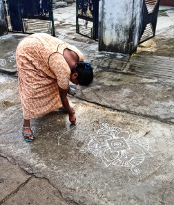 Lady making a rangoli in front of her house, early AM