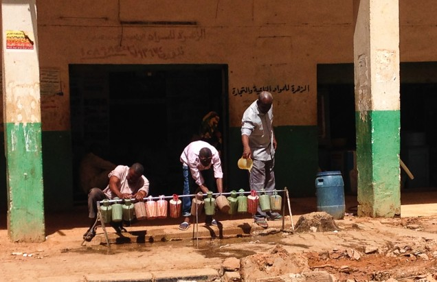 A row of plastic washing jugs, one man filling them and two men having a wash before prayers.