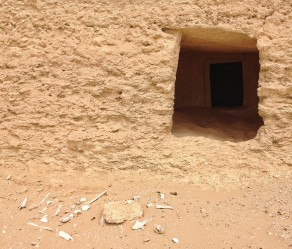 Bones scattered in front of an opened tomb.