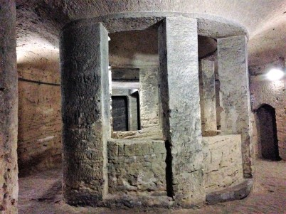 Looking across a well-like structure in the catacombs.