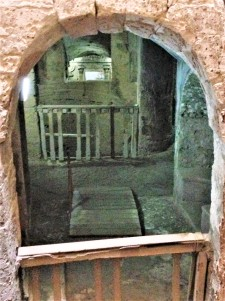 Looking from the spiral staircase through carefully placed arched windows into the depths of the catacombs.