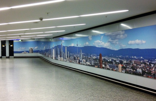 A photo of a hall at Frankfurt Airport with a nice mural of Frankfurt.