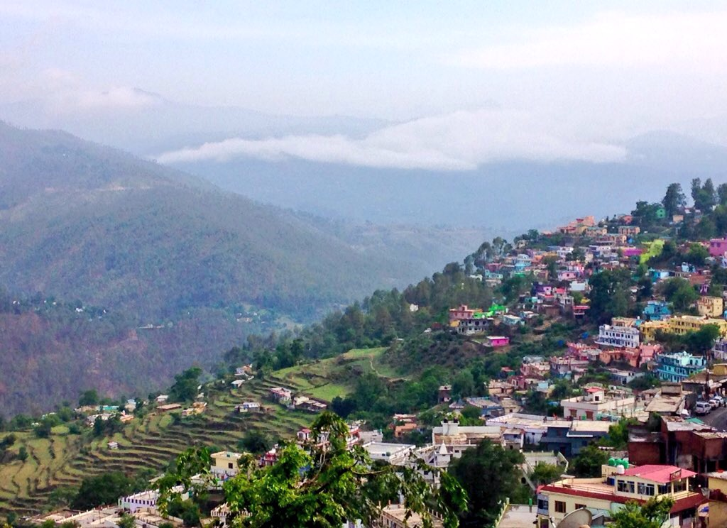 Photo of houses and planted terraces cascading down the sides of the mountain ridge where Almora is located in the state of Uttarakhand.