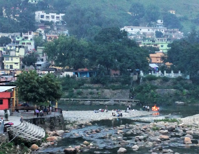 A view of the confluence of the Gomti and Saryu rivers with a funeral fire burning where they meet. Baghunath Temple, Bageshwar, Uttarakhand.