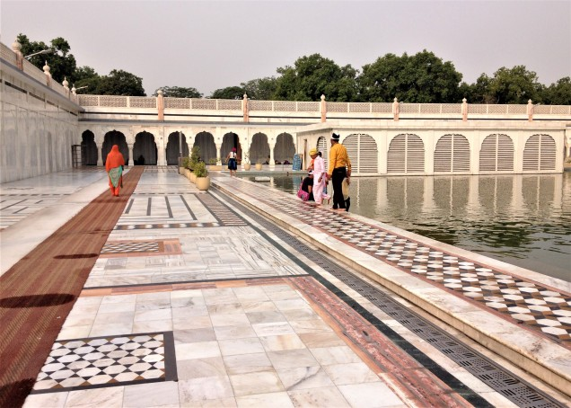 A corner of the holy pond at Gurudwara Bangla Sahib, New Delhi, with family group. Photo shows marble surround with inlaid decorations.