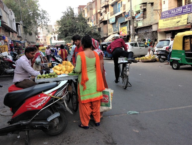A street shot in Pahar Ganj, Delhi, showing a lady buying mangos from a street vendor.
