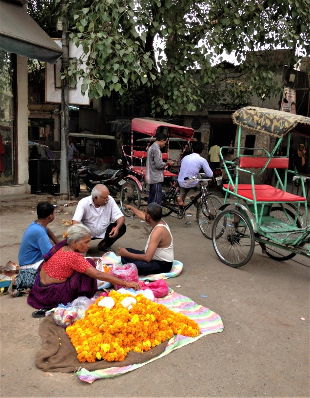 A lady with a heap of marigolds, with several men and two traditional cycle rickshaws behind. Pahar Ganj, Delhi.