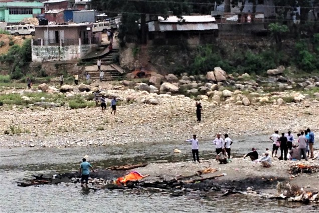 Confluence of Saryu and Gomti rivers, and men carrying wood down to the burning site for the day's funeral fires. Bhagnath Temple, Bageshwar, Uttarakhand.
