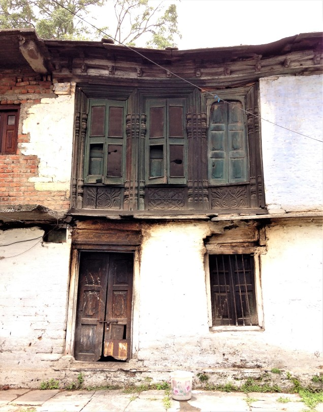An old brick and stucco house in Almora, with traditional decorated wooden windows. Uttarakhand