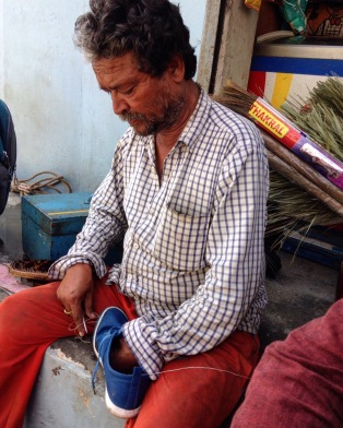 Anand repairs shoes on the stoop of a shop in Chota Bazaar.
