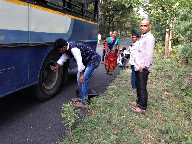 Passenger helping to change the wheel of bus in eastern ghats, Andhra Pradesh