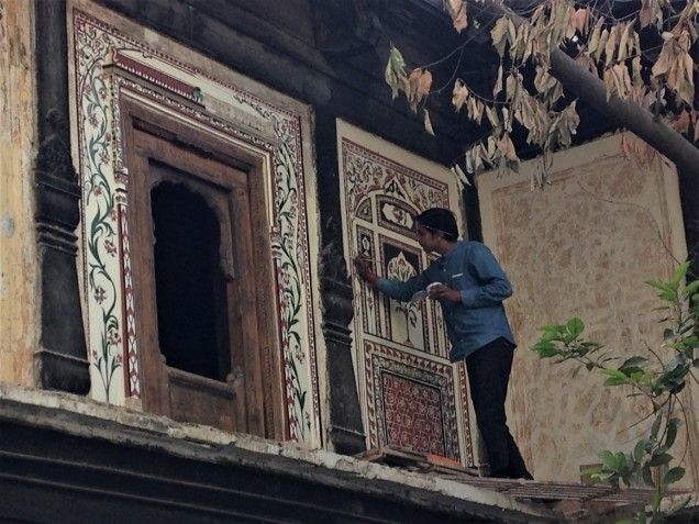 Artist restoring old paintings on building surrounding the old Krishna temple, Indore, Madhya Pradesh.