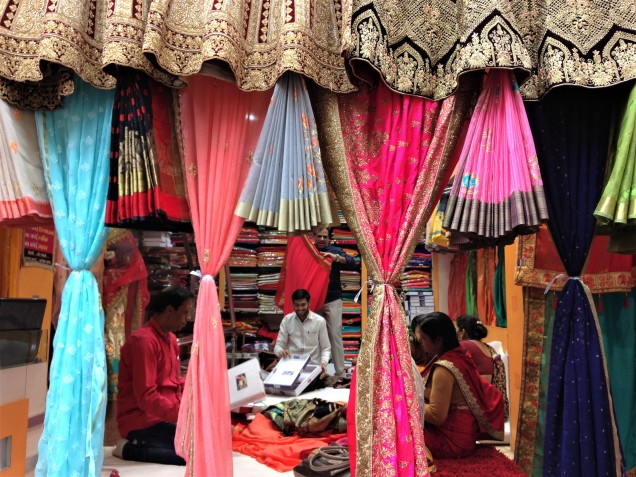 Looking through a curtain of colorful saris into a sari shop, with the proprietor showing saris to some ladies. Cloth market district, Indore, Madhya Pradesh.