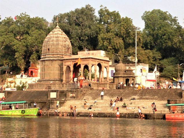 People praying and bathing at Maheshwar ghats, viewed from a boat.