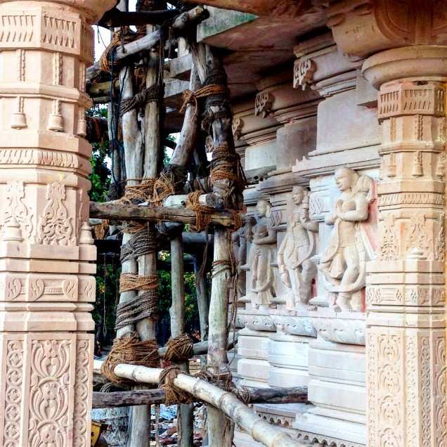 Three sculptures on the tower of the Jain temple, surrounded by scaffolding. Amarkantak, Madhya Pradesh