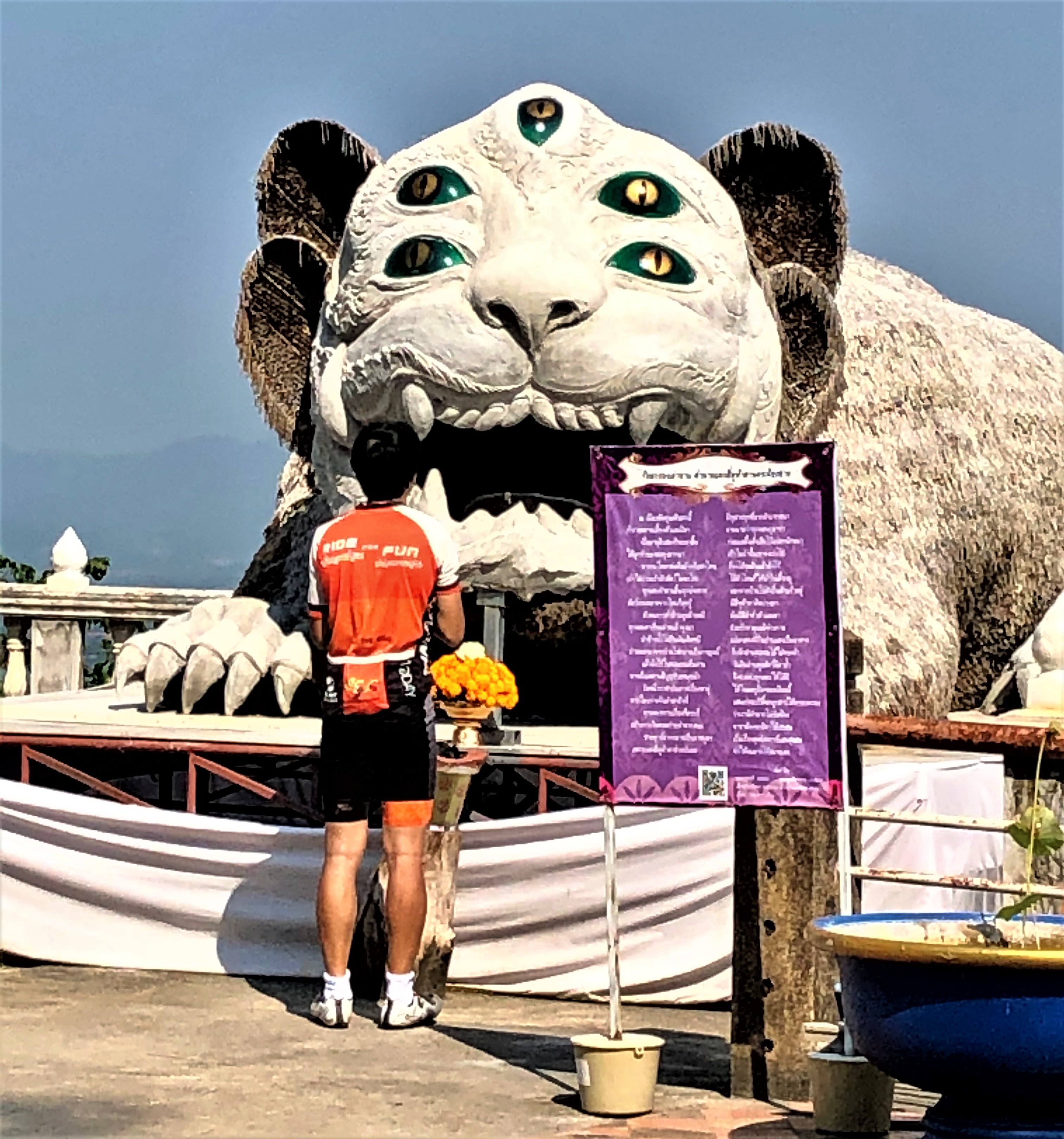 Cyclist making his offering to the large Sihuhata at Wat Phra That Doi Khao Kwai