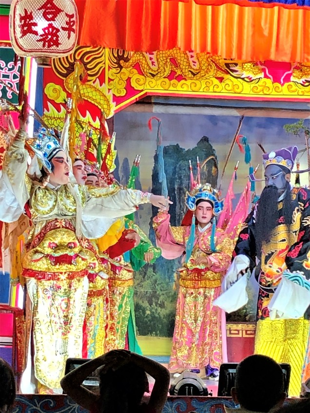 Chinese opera actor gesturing to other actors across the stage