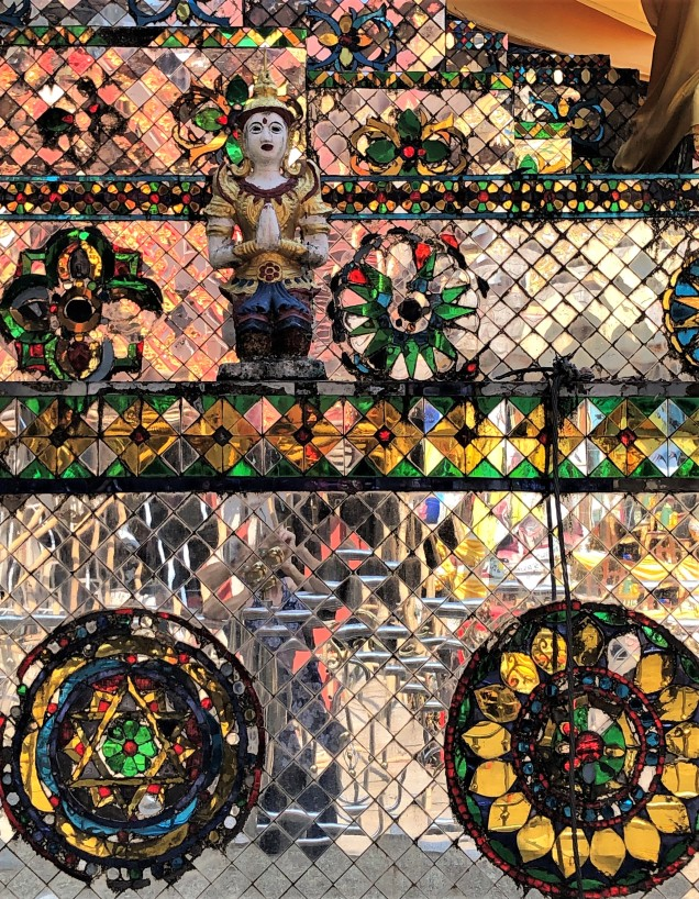 Detail of the surface of the mirrored stupa at Wat Phra That Doi Khao Kwai, showing the colors, the geometric designs and the uneven surface.