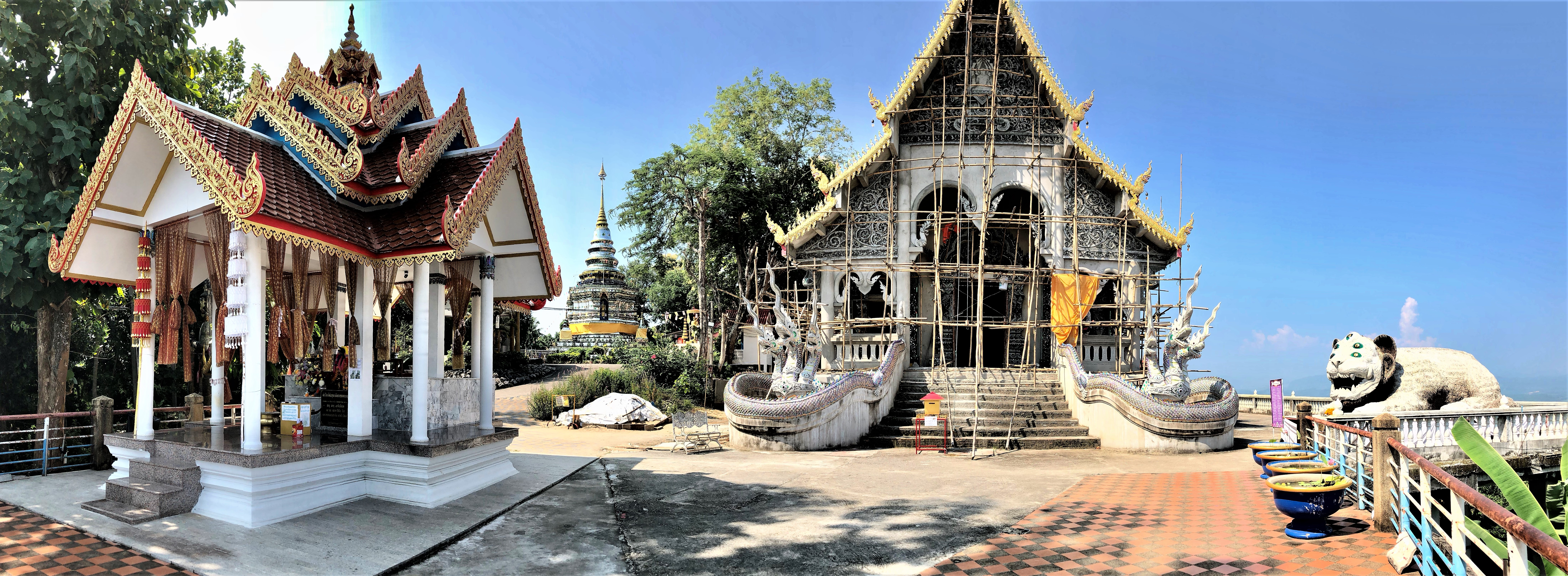 Panoramic photo encompassing the small Kwan Yin temple, the glass stupa of the main temple, the new Sihuhata temple under construction, and the large sculpture of Sihuhata himself, all under a blue sky. Wat Phra That Doi Khao Kwai, Chiang Rai.