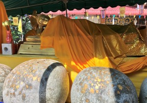 Image of reclining Buddha with round boulders in front, ornamented with gold leaf.